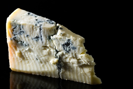 12332799 - piece gorgonzola cheese isolated on black with reflection