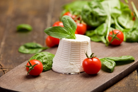 11969382 - ricotta cheese with basil leaves and cherry tomatoes on wooden table